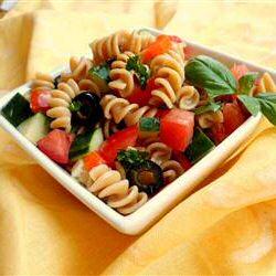 Koude pastasalade met rotini, komkommer, ui, kerstomaten, zwarte olijven en blaadjes basilicum
