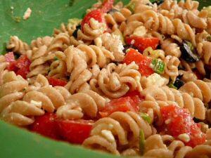 Koude pasta salade met tomaat, olijven, ui, fetta kaas en vinaigrette