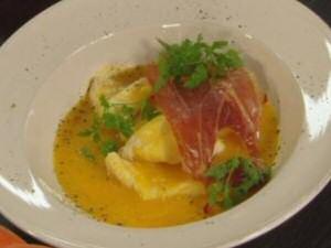 Een bord pompoensoep met gebakken gandaham en gepocheerde visfilets volgens een recept van Piet Huysentruyt